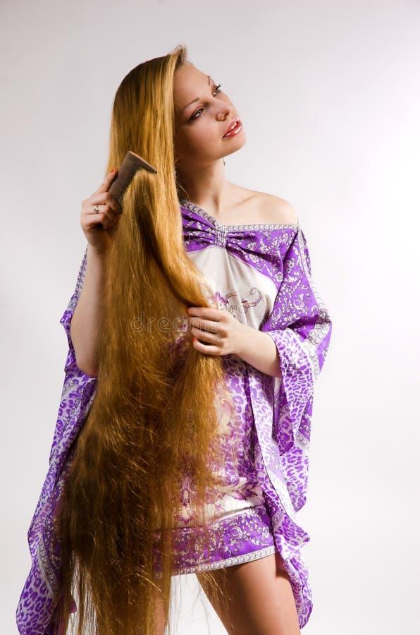 La fille peigne le long cheveu image stock