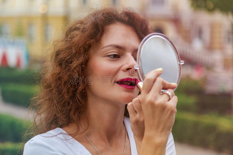 La fille peint des lèvres sur la rue photos libres de droits
