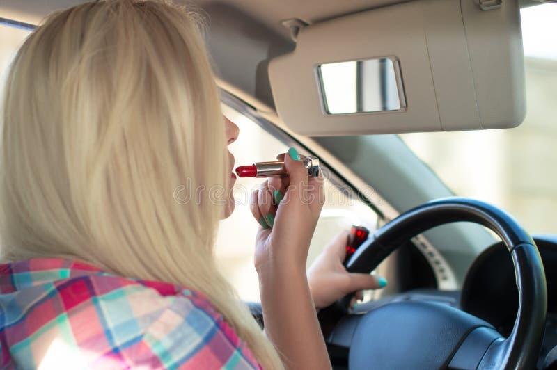 La fille peint ses lèvres tout en conduisant une voiture photographie stock libre de droits