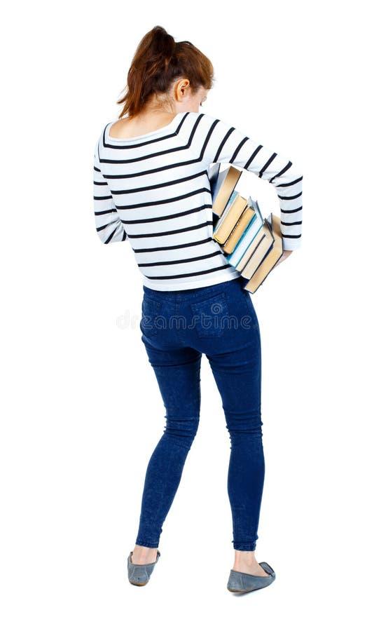La fille porte une pile lourde des livres Vue arrière image libre de droits