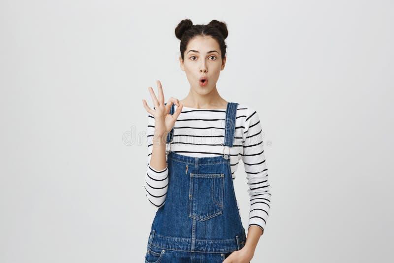 La fille positive avec les cheveux foncés dans les hairbuns dans des vêtements de denim montre le signe correct, démontre que tou photographie stock
