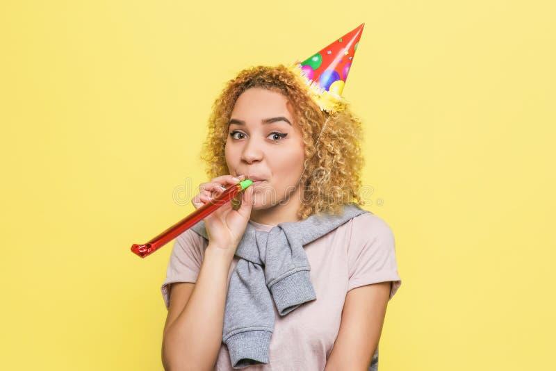 La fille positive tient un wistle et souffle quelques cheveux dans eux Également elle a un chapeau d'anniversaire sur sa tête La  images stock