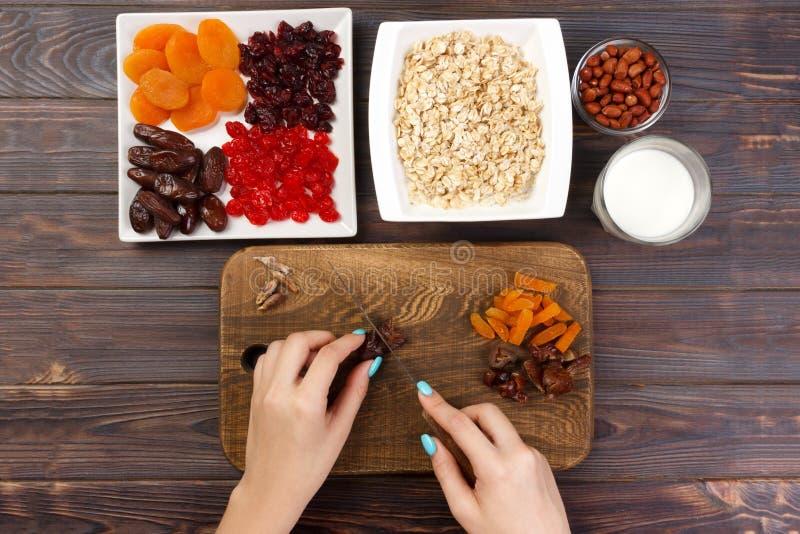 La fille prépare son petit déjeuner que la fille coupe son fruit de date en gruau de farine d'avoine sur une planche à découper C photos stock