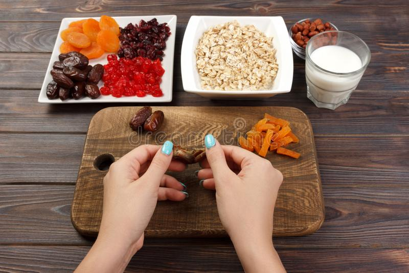 La fille prépare son petit déjeuner que la fille dégage son fruit de date en gruau de farine d'avoine sur une planche à découper  photo stock