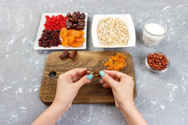 La fille prépare son petit déjeuner que la fille dégage son fruit de date en gruau de farine d'avoine sur une planche à découper  photo libre de droits