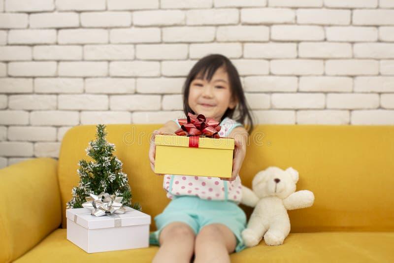 La fille présente un cadeau de Noël fille montrant le boîte-cadeau Enfant asiatique mignon tenant une boîte de Noël An neuf heure photographie stock libre de droits