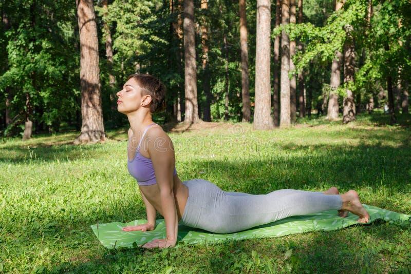 La fille pratique le yoga en parc un jour ensoleillé photographie stock