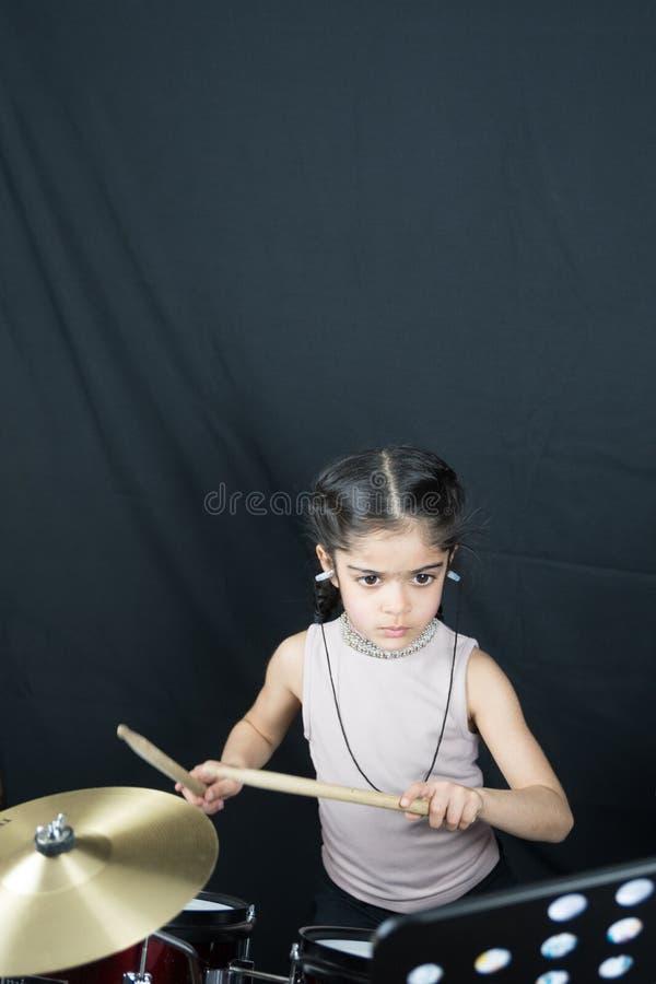 la fille 5 an pratique les tambours photo stock