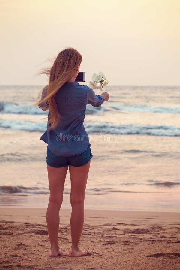 La fille prend des photos de fleur de Plumeria photographie stock libre de droits