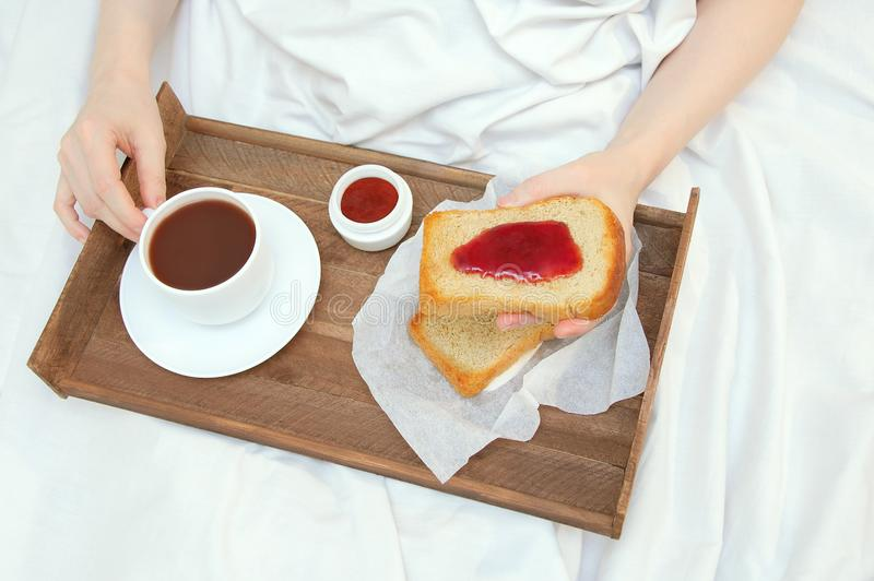 La fille prend le petit déjeuner dans le lit photographie stock