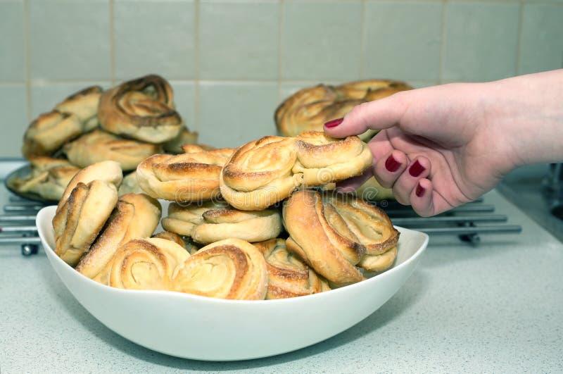 La fille prend le petit pain cuit au four appétissant savoureux du plat photo libre de droits