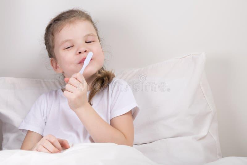 La fille prend soin de ses dents, et se livre ne pas sortir du lit photos stock