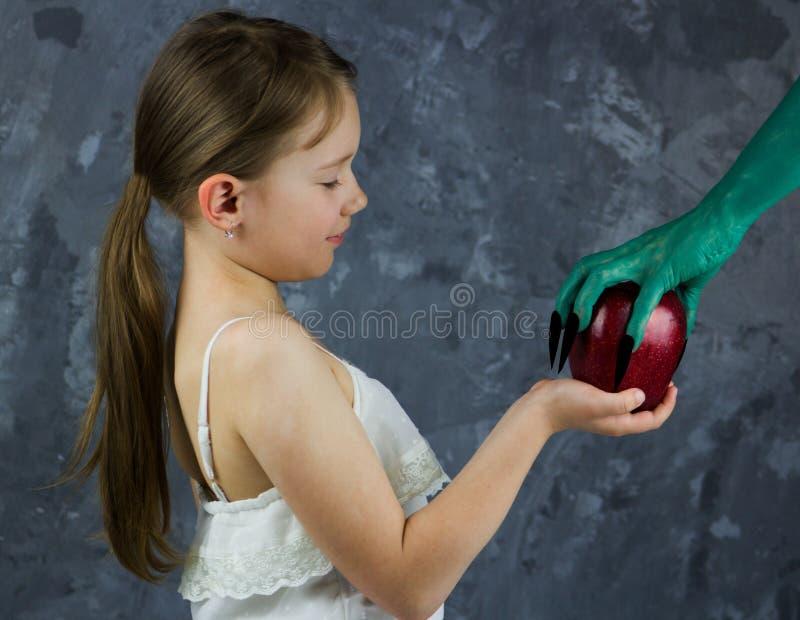 La fille prend une pomme de la sorcière Le conte de fées de blanc de neige photo stock