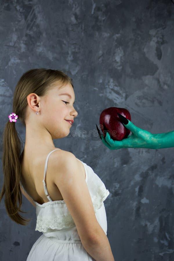La fille prend une pomme de la sorcière Le conte de fées de blanc de neige images libres de droits