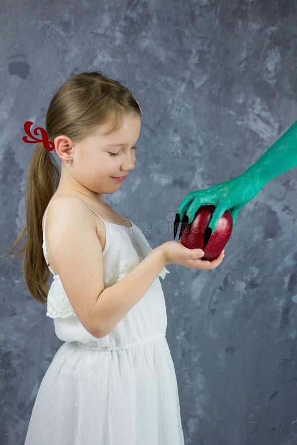 La fille prend une pomme de la sorcière Le conte de fées de blanc de neige image libre de droits