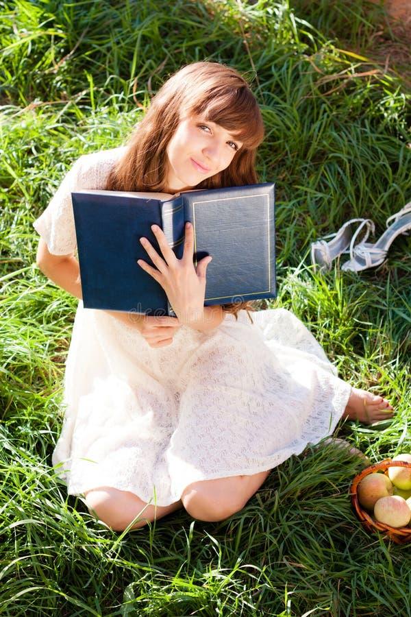 La fille a pressé son livre et sourires rêveusement photo stock