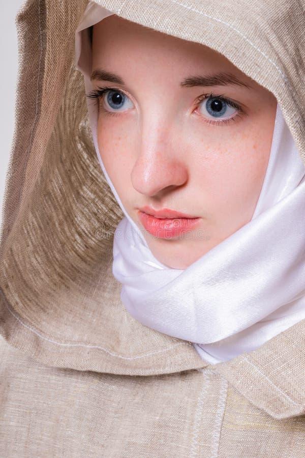 La fille pure attirante avec un regard clair dans une écharpe blanche adresse la prière à Dieu photos stock