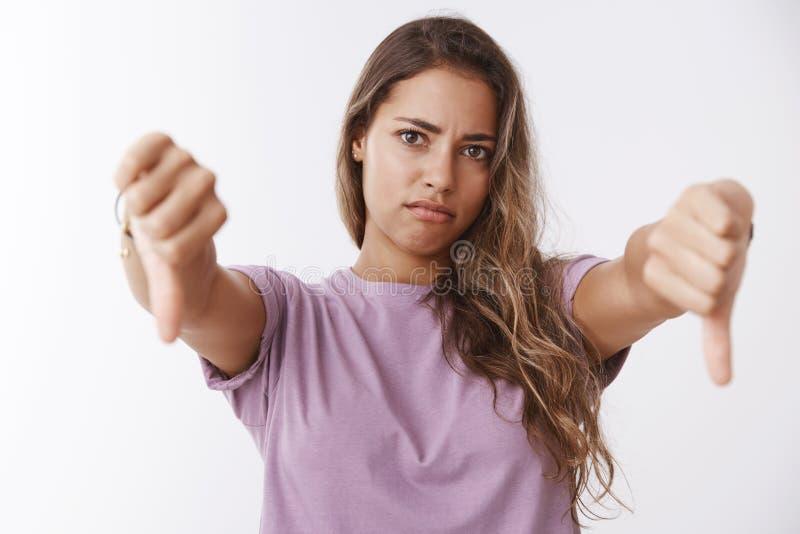 La fille réagissant la mauvaise idée terrible, montrant des pouces en bas de la désapprobation grimaçante, sont en désaccord déte photo stock