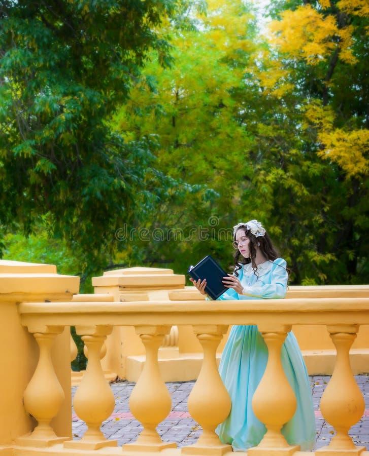 La fille réfléchie dans une robe bleue de cru lit une histoire d'amour images libres de droits