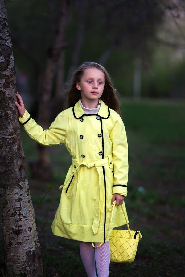 La fille réfléchie mignonne dans un imperméable jaune avec de longs cheveux marche au printemps le parc avec un sac à main photographie stock libre de droits