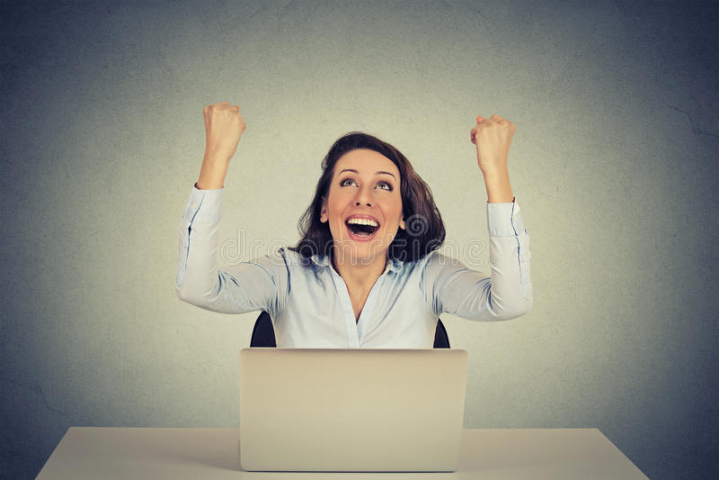 La fille réussie avec des bras a augmenté utilisant un ordinateur portable image libre de droits