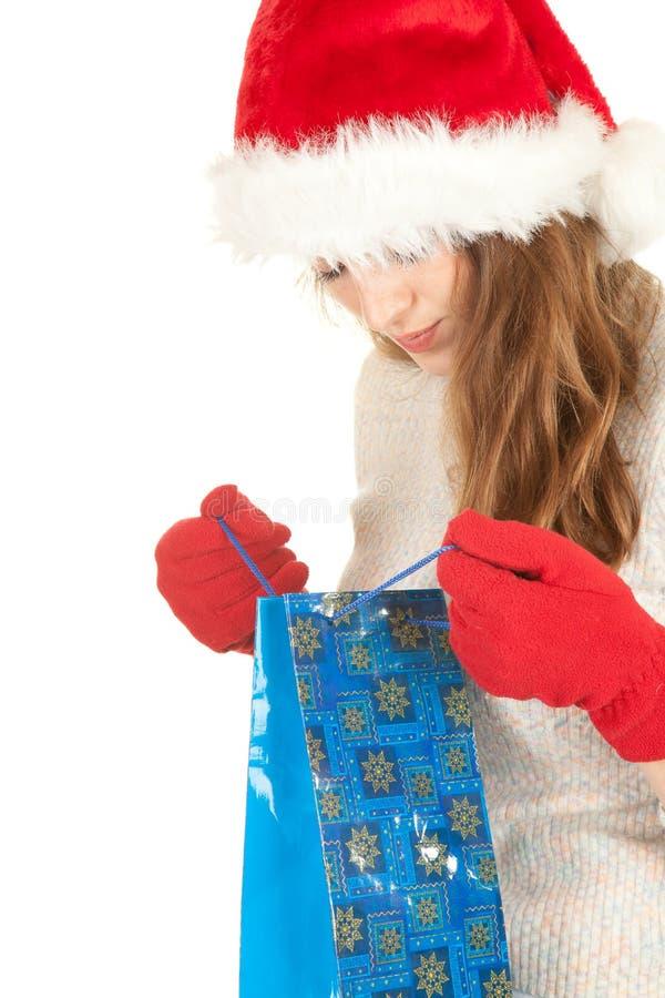 La fille a rectifié dans le sac à provisions de transport de chapeau de Santa photo stock