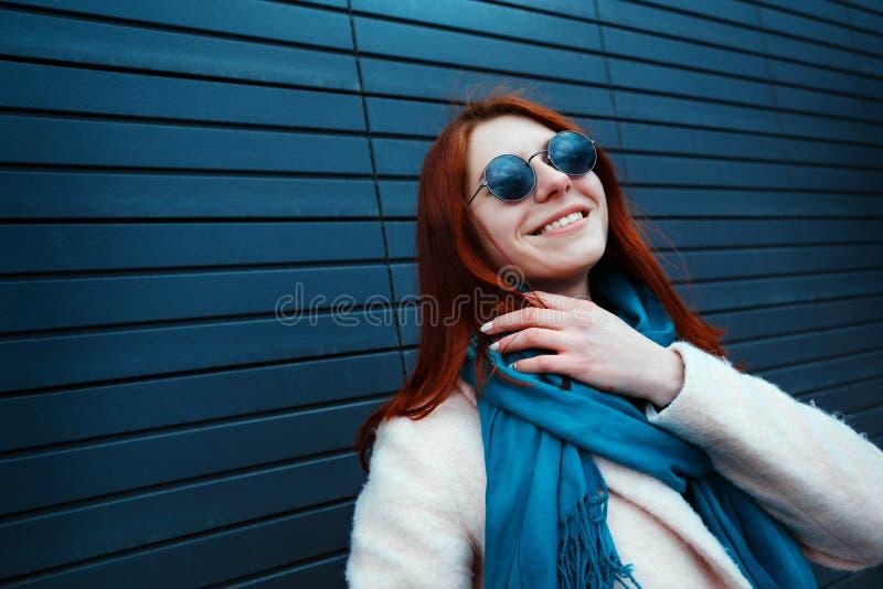 La fille redhaired de hippie dans des lunettes de soleil élégantes pose devant un mur noir sur la rue photographie stock