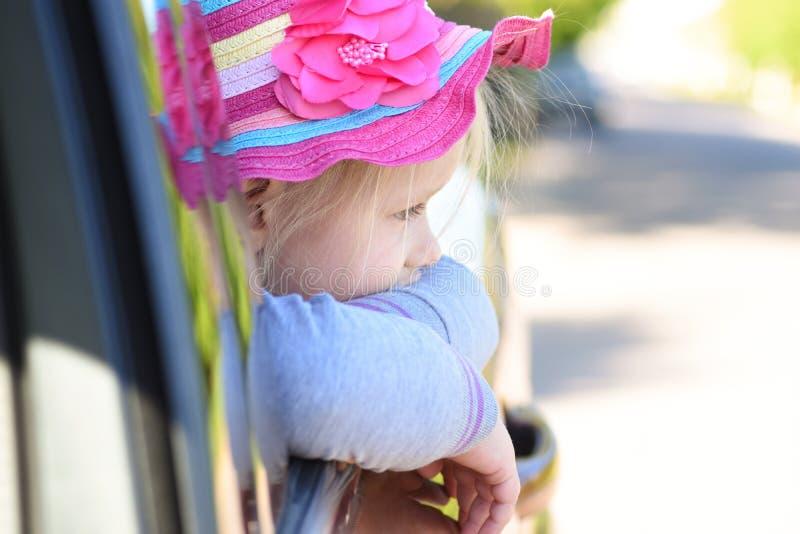 La fille regarde la fenêtre d'une voiture tout en montant image stock