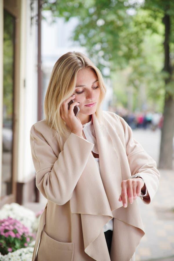La fille regarde l'horloge et parle au téléphone photo stock
