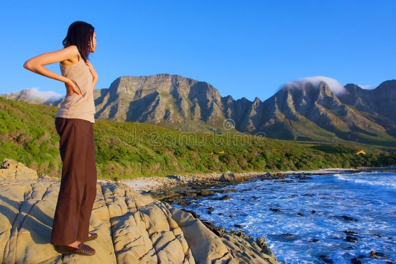 La fille regarde la mer et les montagnes impressionnantes photo stock