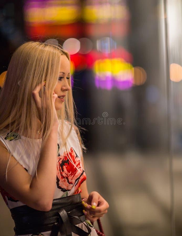 La fille regarde la vitrine de nuit photos stock