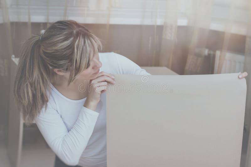 La fille regarde vers le bas tout en se tenant avec une feuille de papier ou choisit le papier peint photo stock