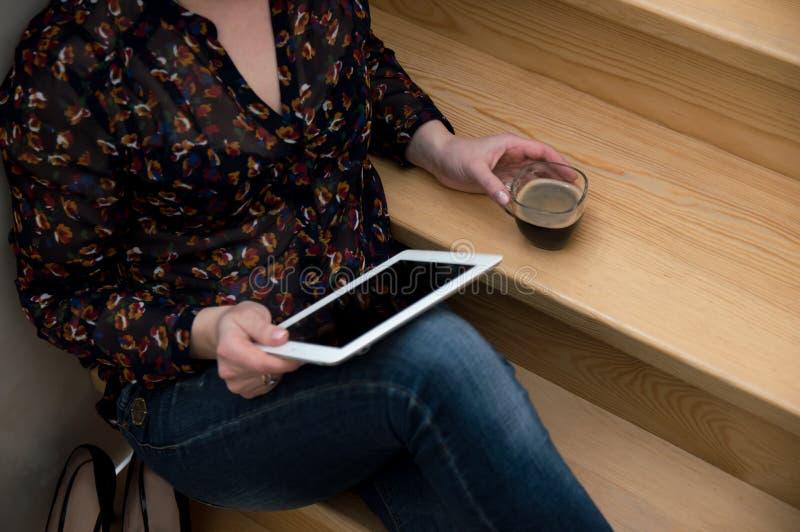 La fille repose et regarde l'écran du comprimé, lit les nouvelles, boit du café Travail ? la maison Femme d'affaires à la maison  photo stock
