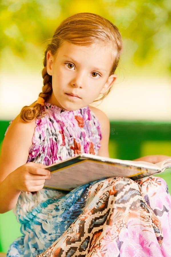 La fille repose le livre de relevé images stock