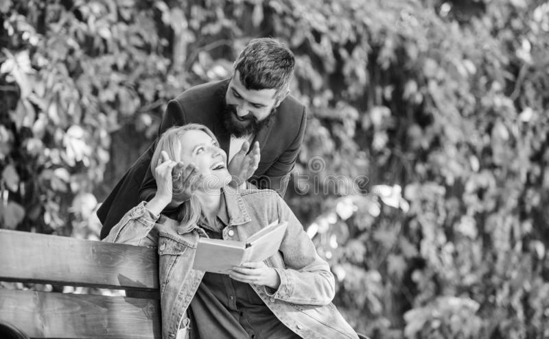 La fille reposent le livre lu par banc tandis qu'ami d'attente Attendez-le la date Dater en parc Concept romantique de relations  photographie stock libre de droits