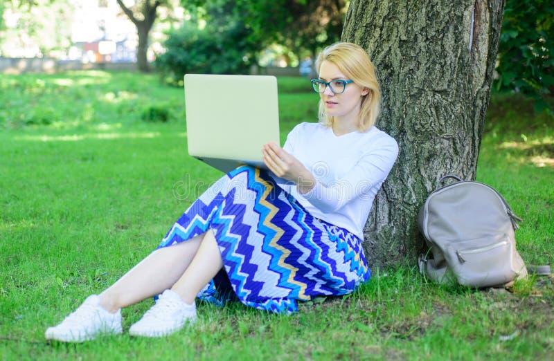 La fille reposent le tronc d'arbre maigre d'herbe avec le carnet Indépendant de Madame travaillant en parc Libre accès de connexi photo libre de droits
