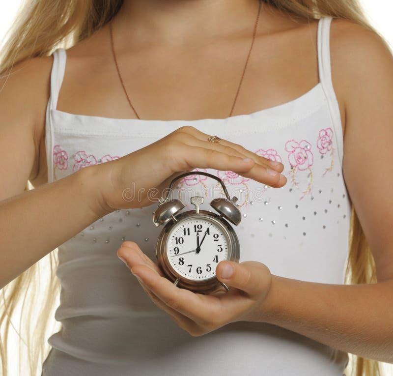 La fille retient une horloge d'alarme dans des mains images libres de droits
