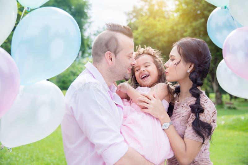 La fille riant heureusement après parent l'embrassent image stock