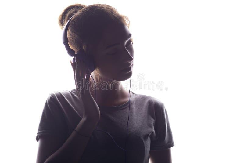 La fille romantique écoutant la musique dans des écouteurs, jeune femme détendant sur un blanc a isolé le fond image stock