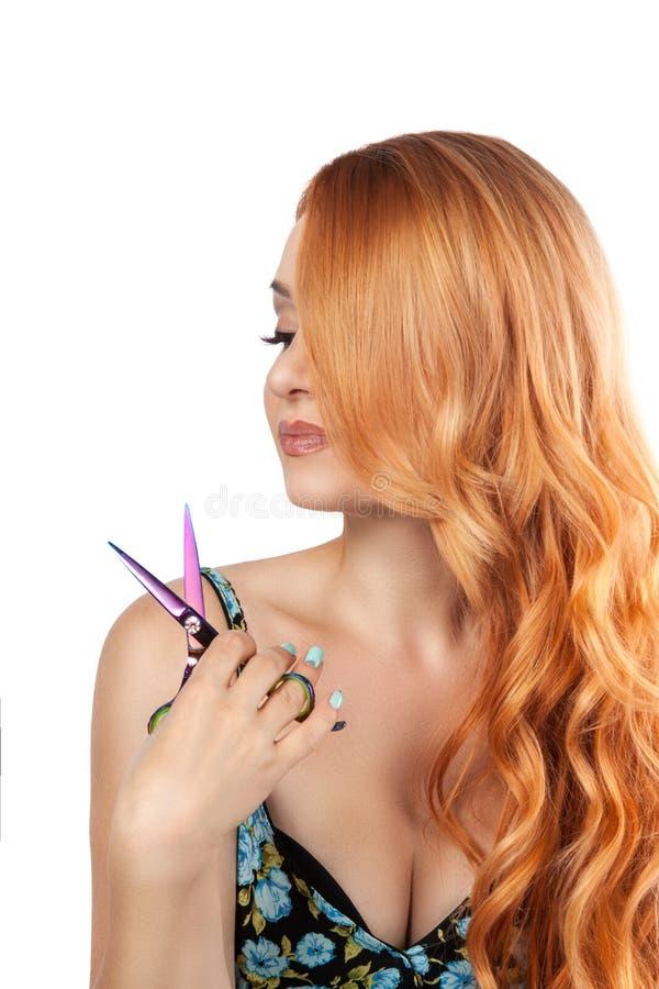 La fille rousse aux cheveux longs avec des ciseaux coupe les cheveux photographie stock libre de droits