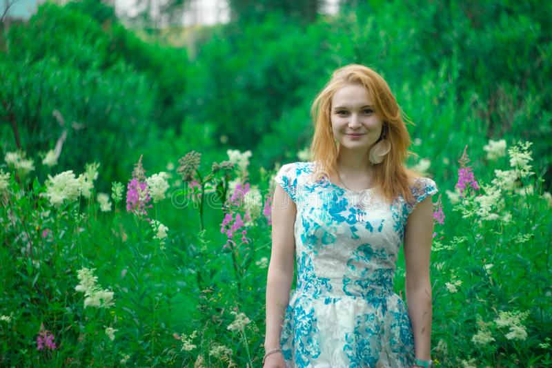 La fille rousse dans l'herbe verte images stock