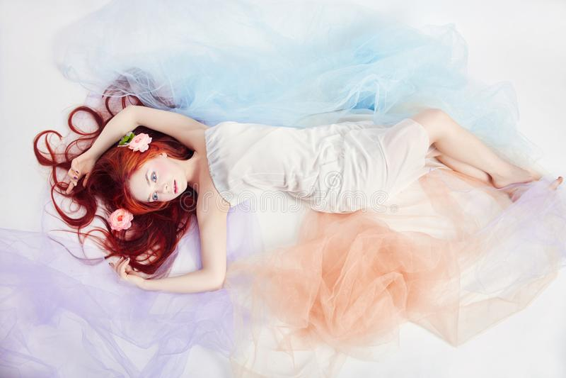 La fille rousse dans la robe colorée bien aérée légère se trouve sur le fond de blanc de plancher Belles fleurs dans des cheveux  image stock