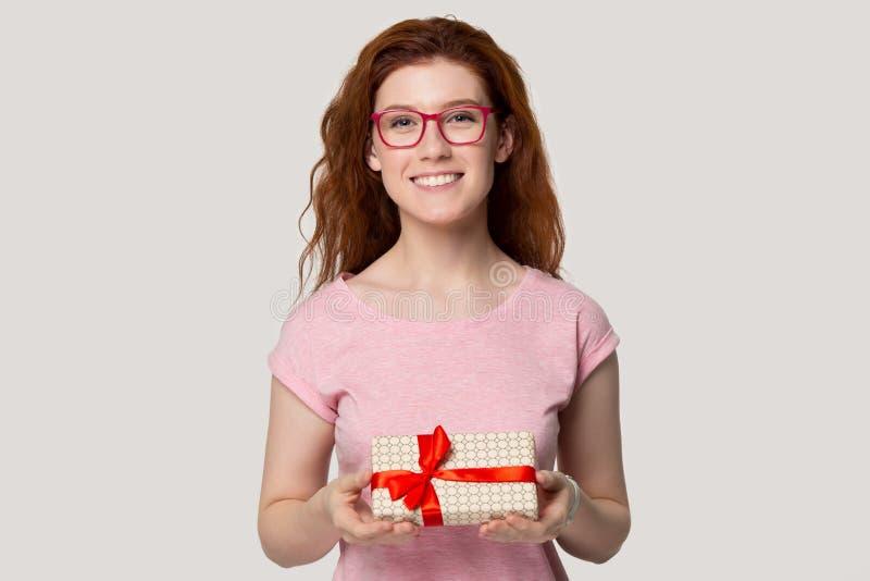 La fille rousse de sourire font le boîte-cadeau se tenant actuel images stock