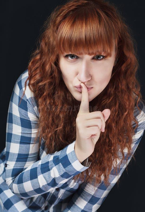 La fille rousse fait un geste du silence photos stock