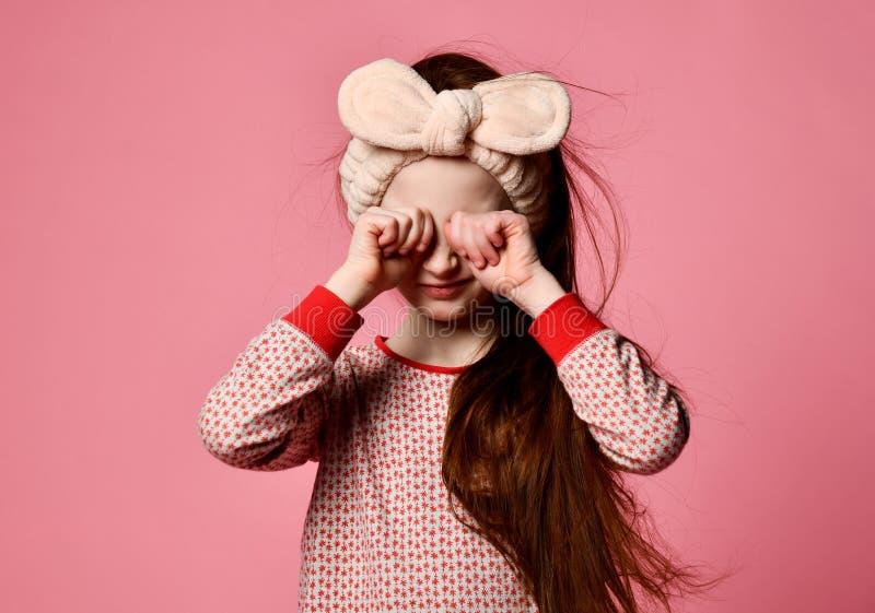 La fille rousse mignonne dans des pyjamas a réveillé et a frotté ses yeux image libre de droits