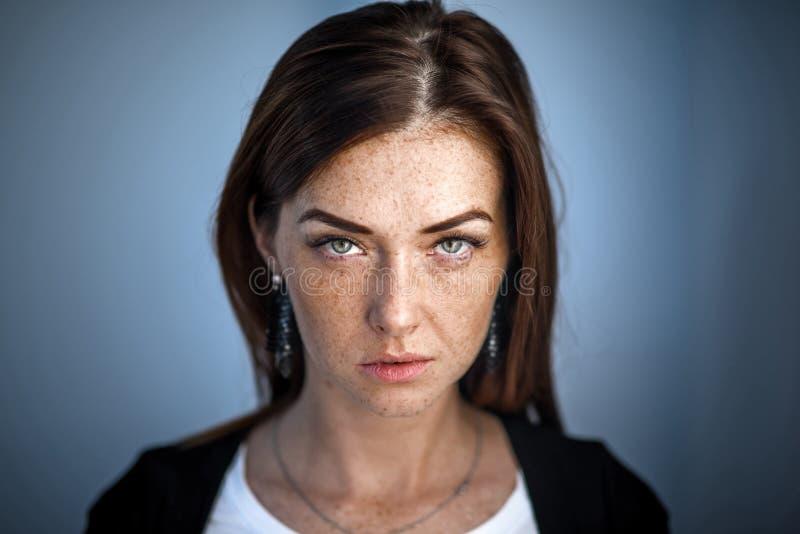 La fille rousse mignonne regarde dans la caméra Fille moderne dans un milieu urbain Visage de taches de rousseur image libre de droits