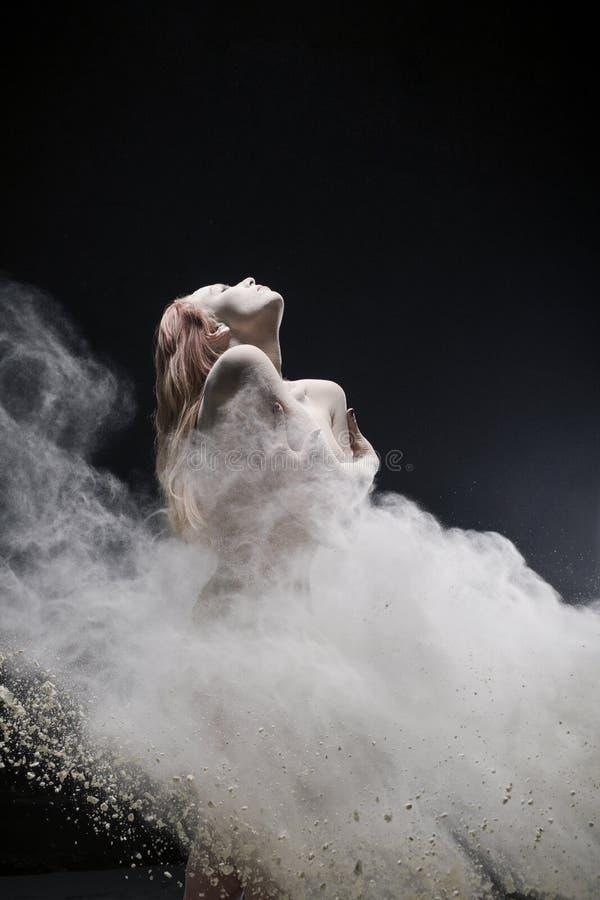 La fille rousse nue a tiré en nuage de poussière blanc photographie stock libre de droits