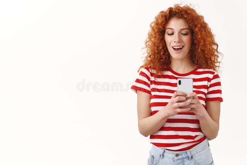 La fille rousse prenant l'ami d'image enregistrant secrètement le smartphone visuel semblent espiègle ayant l'amusement souriant  photo stock