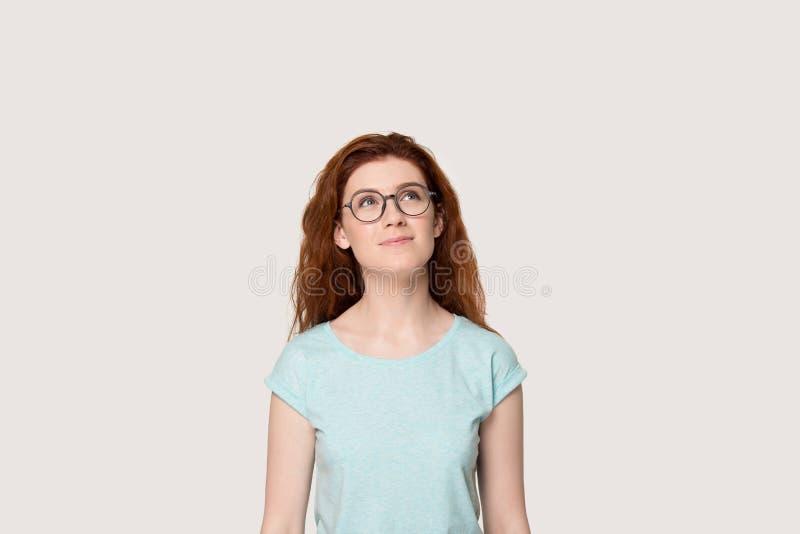 La fille rousse rêveuse en verres recherchent imaginante photo libre de droits