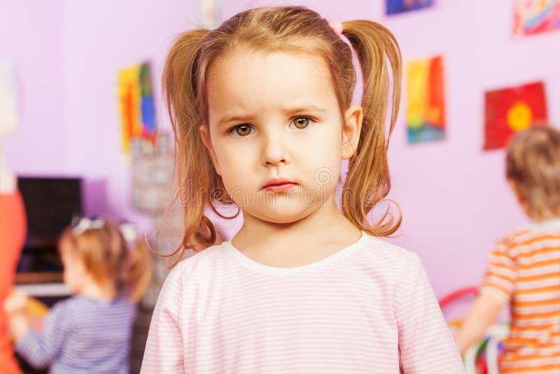 La fille sérieuse calme avec des amis jouent sur le fond image stock